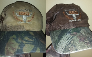 mossy oak hat with elk on the side and the stumbling steer bbq logo on front